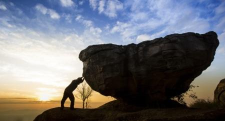Man pushing a boulder on a mountain